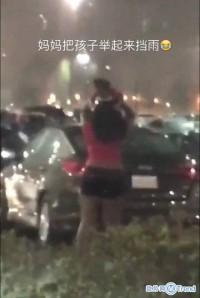妈妈把孩子举起来挡雨 绝对是亲生的